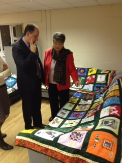 Chairperson of RFJ Clara Reilly shows Mr De Greiff some of the Remembering Quilt